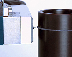 Automated pneumatic grease dispenser, the Liquidyn® jet valve, dispenses grease sideways onto a rotating cylinder to demonstrate the ability to dispense from any angle.