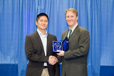 Jonathan Doan, Nordson MARCH, accepts award from Mike Buetow, editor Circuits Assembly